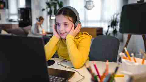 Child with headphones using laptop computer for online learning.
