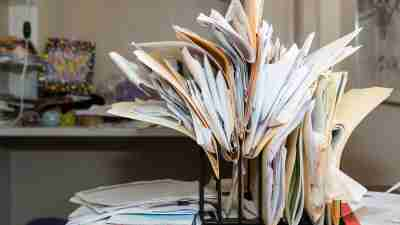 A cluttered desk - folders teeming with paperwork and stacked on top of one another.