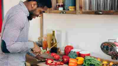 Man cutting a bell pepper in his kitchen.