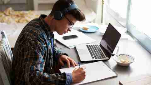Teenage boy wearing headphones and listening to music works at desk in his bedroom