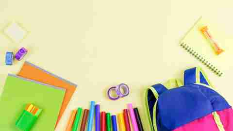 Colorful school supplies laid out on bright background