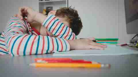 Child laying head on desk with forearm over eyes, tired from remote learning.