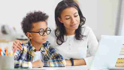 Portrait of cute African boy wearing big glasses while using laptop with mom, homeschooling and remote education concept