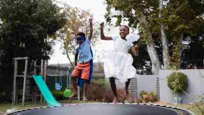Playful siblings in costumes enjoying on trampoline at lawn