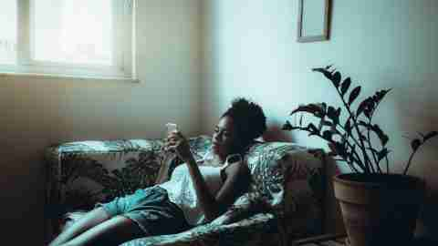 A cute young African-American woman is lazily leafing through internet pages on a smartphone while laying on the sofa near the window and a plant, and being bored with quarantine and isolation