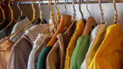 Lots of brightly colored clothes on hangers in the closet. Decluttering the cabinet. Second hand