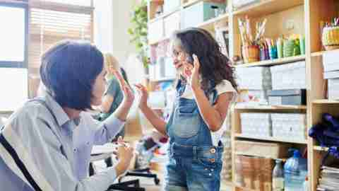 Side view of young female teacher giving high five to adorable girl during art class in school