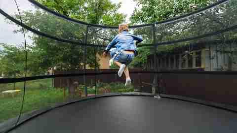 Boy jumping on trampoline in his backyard.