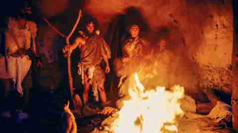 Tribe of Prehistoric Hunter-Gatherers Wearing Animal Skins Stand Around Bonfire Outside of Cave at Night. Portrait of Neanderthal / Homo Sapiens Family Doing Pagan Religion Ritual Near Fire