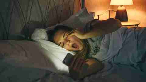 Girl lying in bed uses a cell phone and yawns