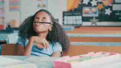 Shot of a young girl looking bored while playing at a school desk