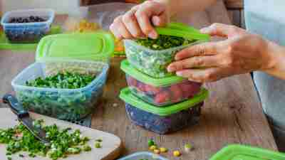 Close up of woman preparing plastic food boxes with fresh green onion, strawberry and blackberry for freezing on the wooden table.
