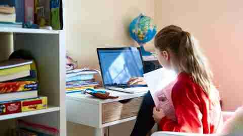 9 year old child sitting at desk doing homework on computer, homeschooling, self development, motivation, improvement