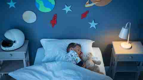 High angle view of little adhd boy dreaming of becoming an astronaut while sleeping with teddy bear in space decorated room.