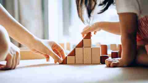 Close up of mother and little daughter sitting on the floor playing with wooden building blocks together and enjoying family bonding time at home