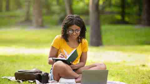 Focused millennial adhd college student black girl writing something in notebook near laptop computer at park, panorama