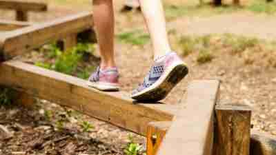 Child leg play balance on wooden beam in park.