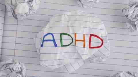 ADHD. Abbreviation ADHD on crumpled paper ball. Close up. ADHD is Attention deficit hyperactivity disorder.