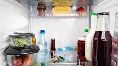Photo of the inside of a refrigerator with a closed door with a bunch of keys between groceries.