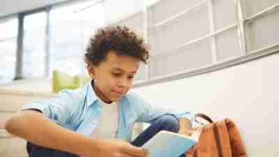 Horizontal medium portrait of curious African American boy reading interesting book sitting alone on stairs, copy space