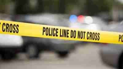 Cordon tape seals off an active crime scene.