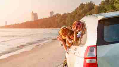 summer fun concept - family in car on the beach
