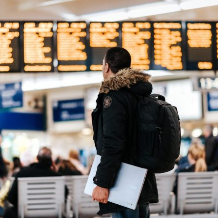 Man looking at huge screen of departures and arrivals in a station or airport