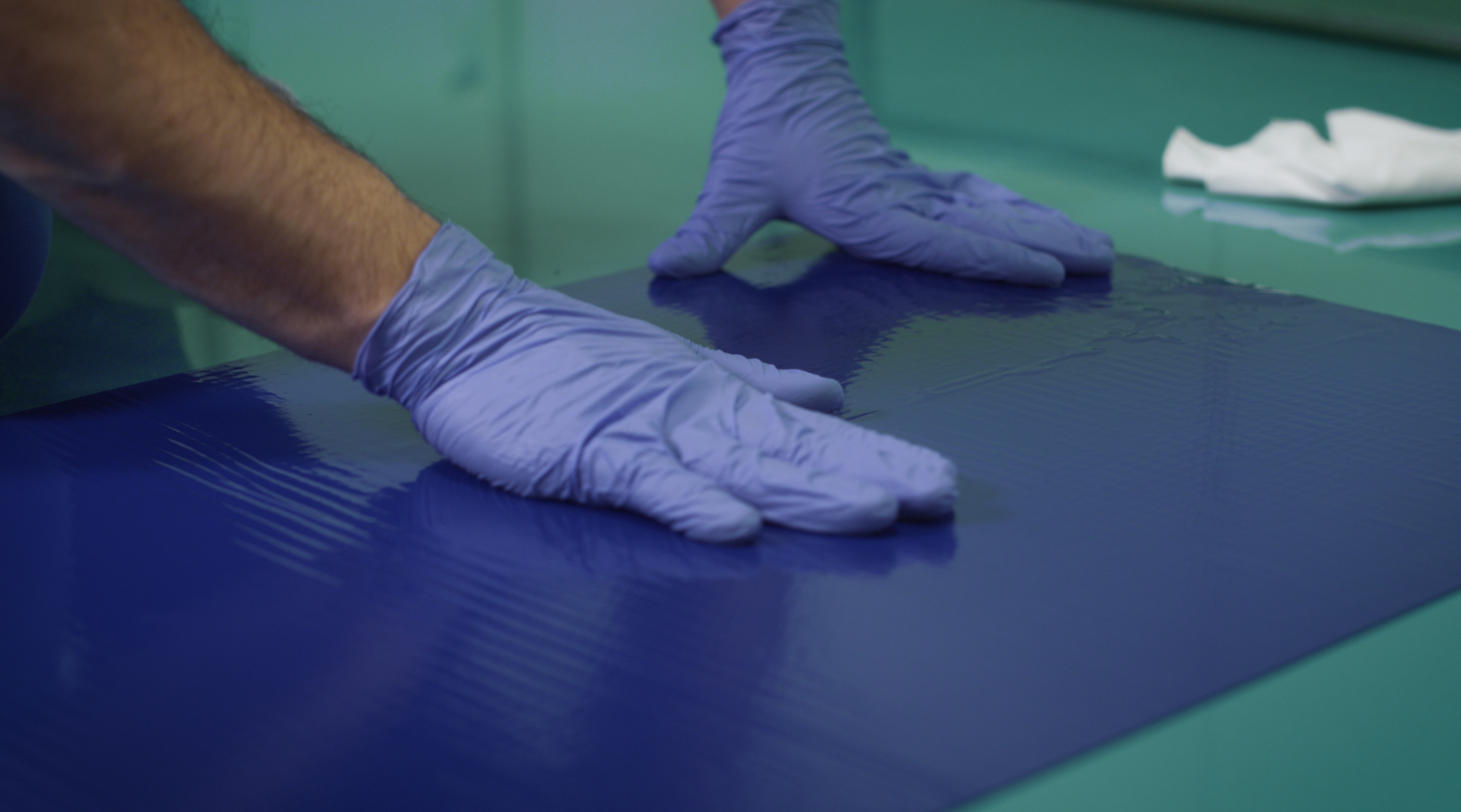 In the picture we can see hands wearing blue gloves, these hands are adhesing a mat on the ground.