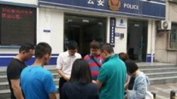 """四川""""秋雨圣约教会""""成员在成都市曹家巷派出所门口祷告(志愿者提供/记者乔龙)"""