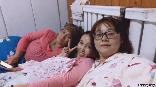"""两名下基层的""""亲戚""""和她们的维吾尔东道主(左)共享一张床(白道仁提供)"""