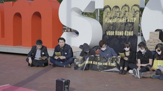 活动的参与者们围坐在广场上合唱《愿荣光归香港》