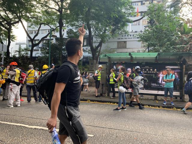 示威民众朝驻守尖沙咀警署警署的持枪员警比中指,表达不满。