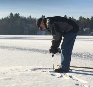 Dean Baker Measures Ice Thickness for Saranac Lake Ice Palace