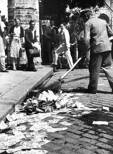 Sweeping up Hungarian banknotes after the Hungarian pengö was replaced in 1946.