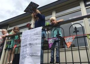 Wieneke Zuydgeest verrast vanaf het balkon haar vader met het Liber Amicorum, gevuld met plaatjes, en verder volgeschreven door familieleden, buren en vrienden