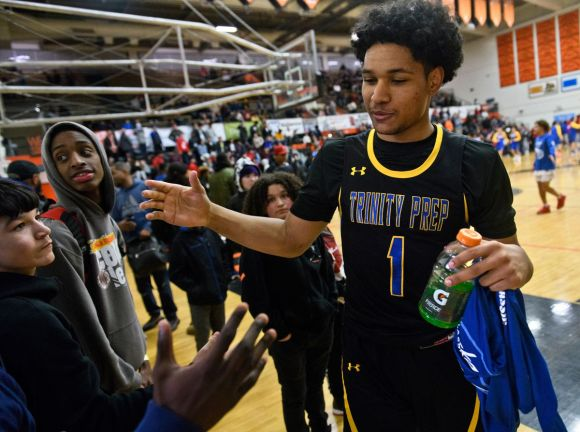 Daishen Nix is greeted by people as he walks off the floor at West High School after a Thursday game at the Alaska Airlines Classic. (Marc Lester / ADN)