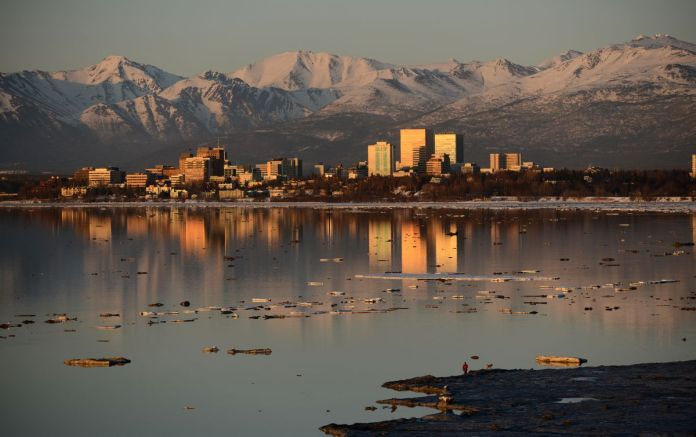 A man and his dog walk on the edge of the ice along Knik Arm with downtown Anchorage and the Chugach Mountains in the background on Tuesday, April 11, 2017. (Bob Hallinen / Alaska Dispatch News)