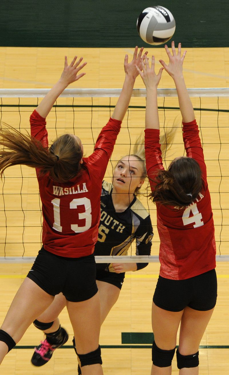 South junior Sarina Gribbin attacks the ball while Wasilla's Kamryn Broach (13) and Kaitlyn Cook (4) try to defend during South's first-round victory over the Warriors. (Bill Roth / ADN)