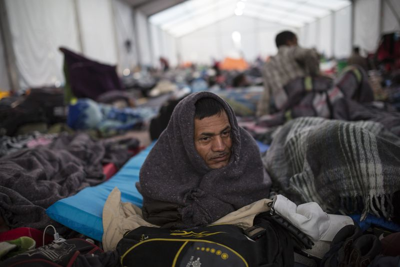 Alcides Padilla, from Honduras, wakes up at the Jesus Martinez stadium in Mexico City, Wednesday, Nov. 7, 2018. Central American migrants on Wednesday continued to straggle in for a rest stop at a Mexico City stadium, where about 4,500 continue to weigh offers to stay in Mexico against the desire of many to reach the U.S. border. (AP Photo/Rodrigo Abd)