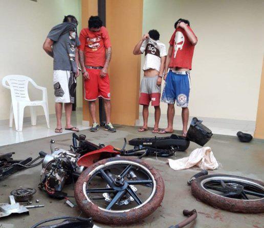 Los aprehendidos junto a las piezas de motocicletas recuperadas.