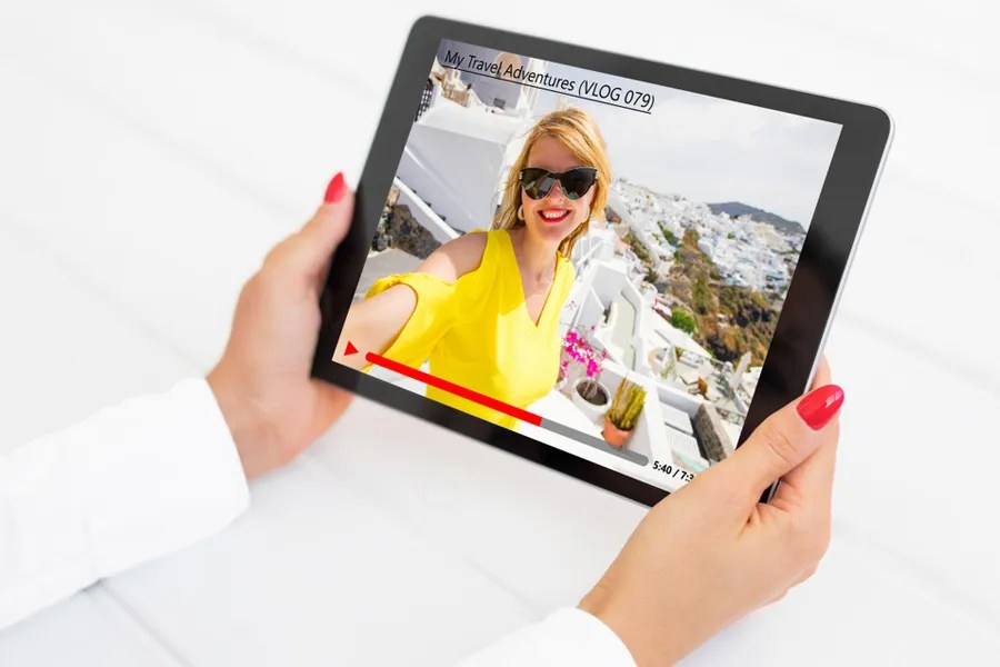 Woman watching a travel vlog on a tablet