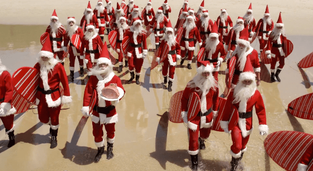 A crowd of Santas stand on a beach. Many carry red and white striped surfboards. One holds a ham up to the camera.