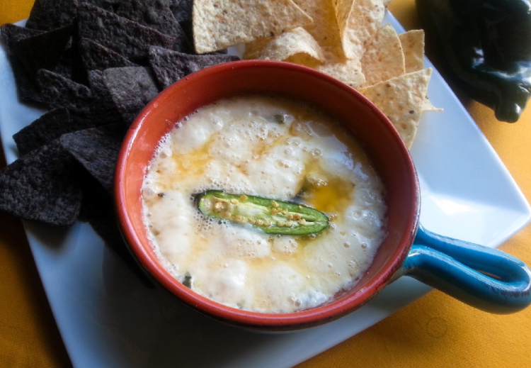 The recipe for the queso fundido has shredded cheese, and poblano peppers. Serving with corn chips for a tasty appetizer.