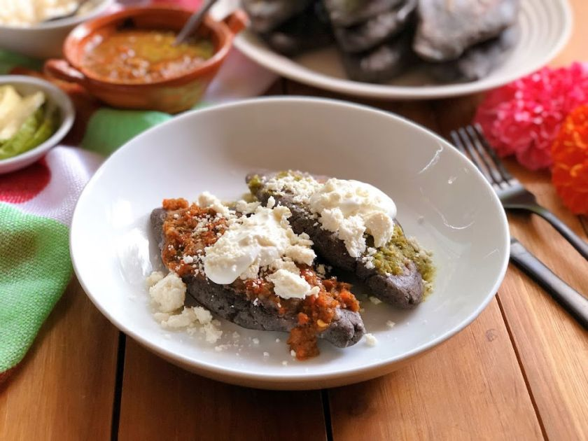 These are the blue corn tlacoyos served with green and red salsa, cream, and crumbled Mexican cheese