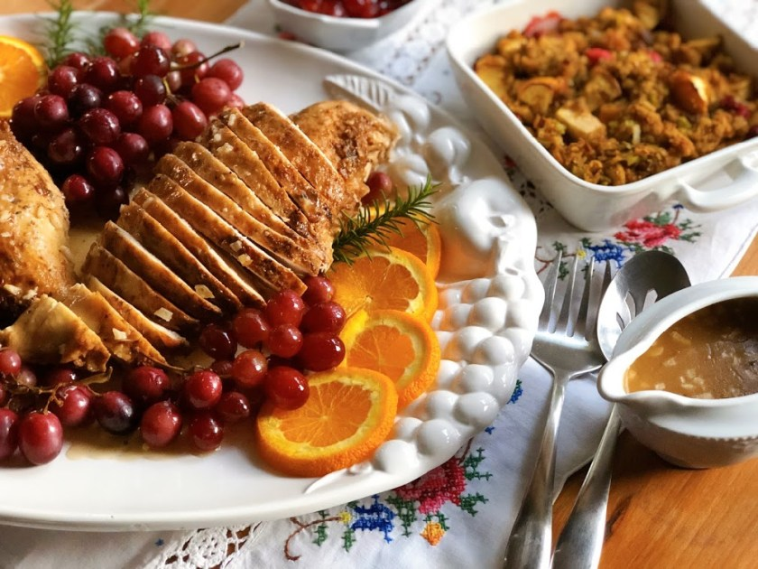 Flavorful roasted garlic turkey dinner with all the fixings, including garlicky gravy, homemade cranberry sauce, bread stuffing, and roasted grapes.