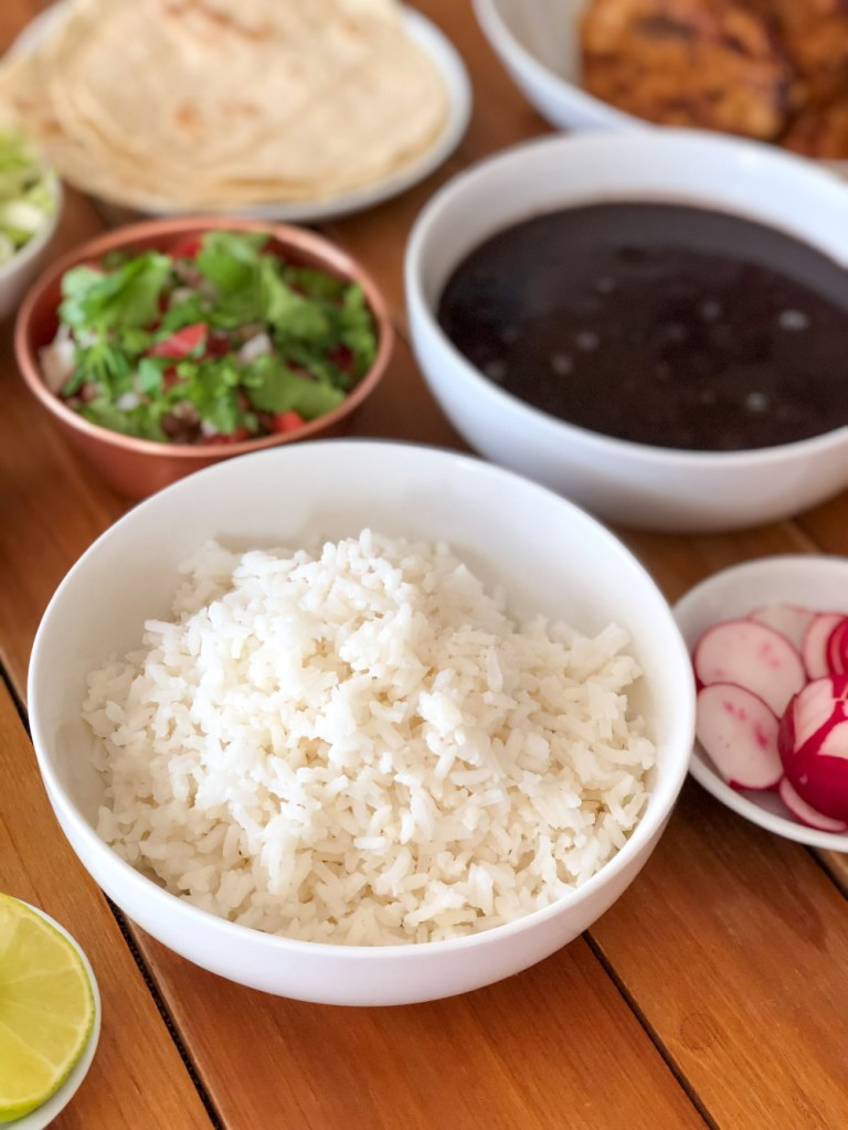 A bowl with white rice, black beans, and other garnishes such as pico de gallo and avocado