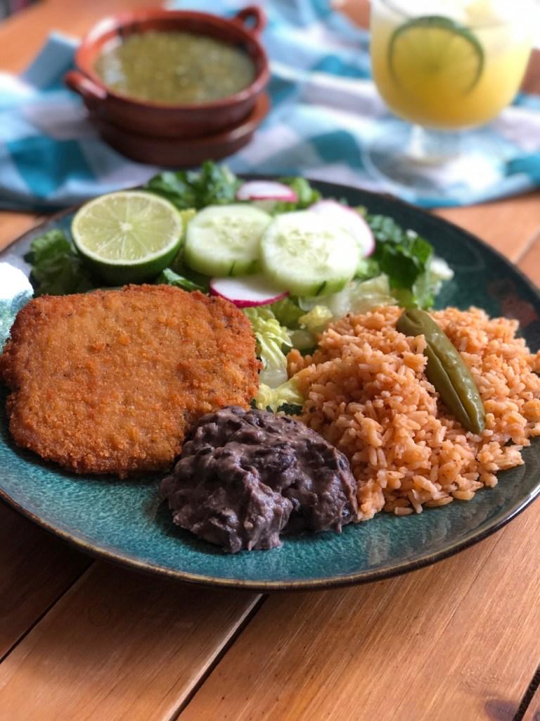 Esta es el platillo de milanesa de cerdo servida con una ensalada verde, arroz mexicano y una guarnición de frijoles negros refritos.