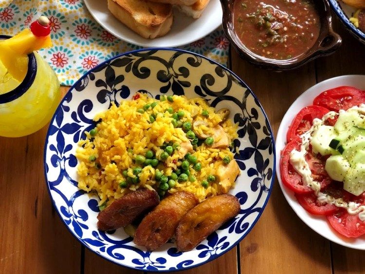Chicken and rice Cuban style served with plantains, tomato and cucumber salad, and buttery Cuban bread toast