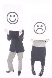 People holding up happy and sad face signs