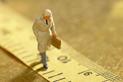 Model of businessman walking along ruler with briefcase